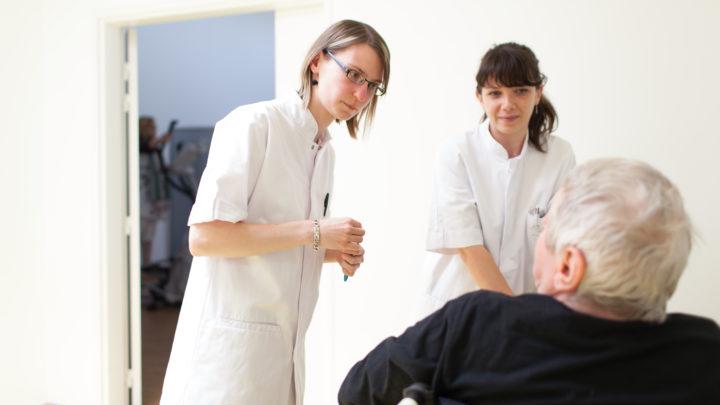Photographie de deux thérapeutes échangeant avec un patient