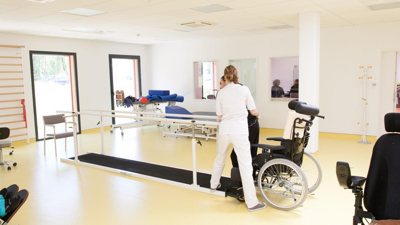 Photographie d'une séance de rééducation, une thérapeute aide un patient à se lever de son fauteuil