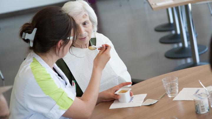 Photographie d'un moment de complicité, une aide soignante aidant une patiente à prendre son repas