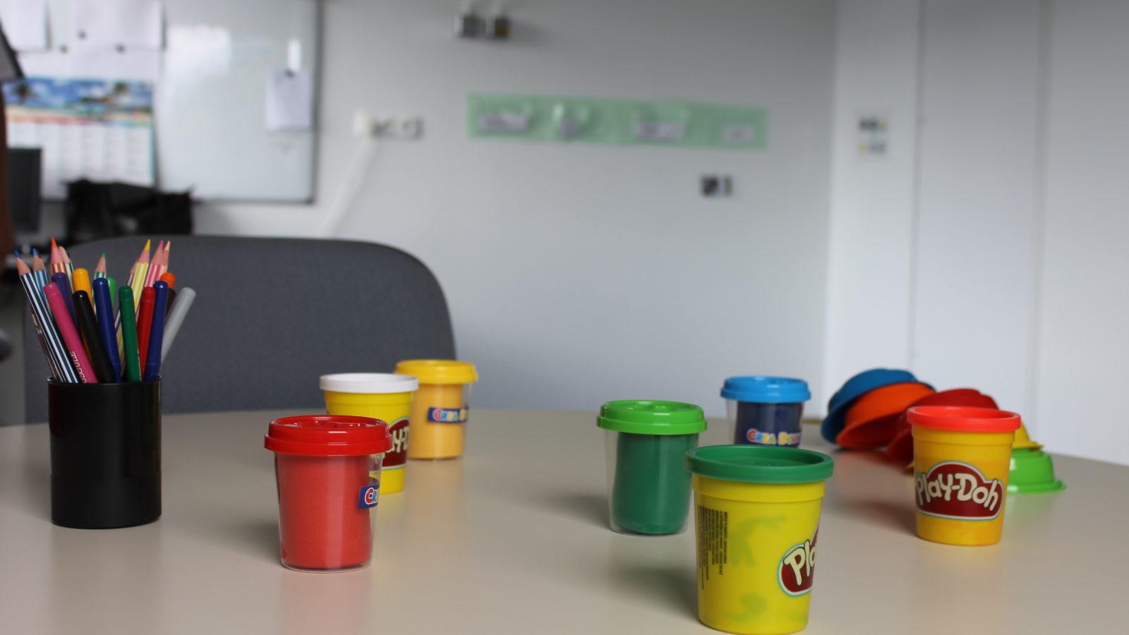 Photographie d'un pot de crayons de couleurs et de pots de pate à modeler posés sur une table.