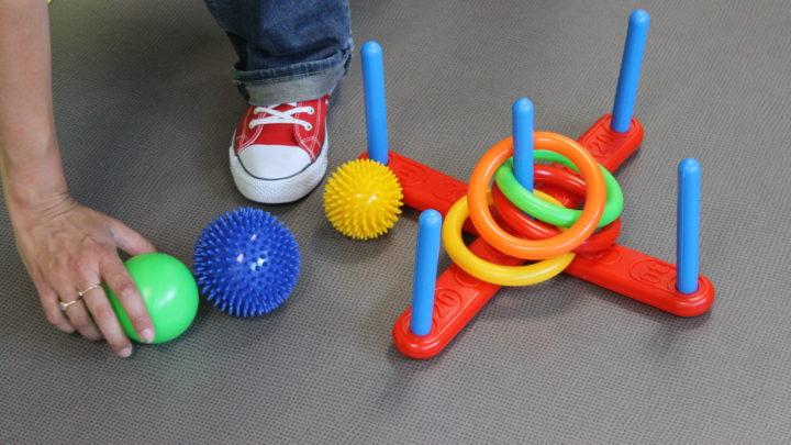 Photographie de la main d'une thérapeute ramassant au sol un jouet pour enfant