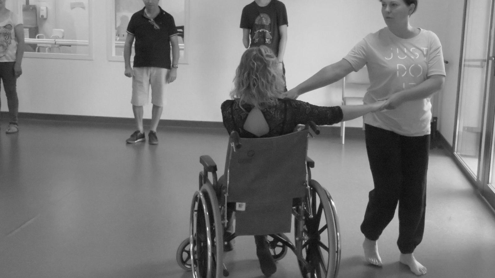 Deux femmes, dont une en fauteuil roulant, qui dansent.