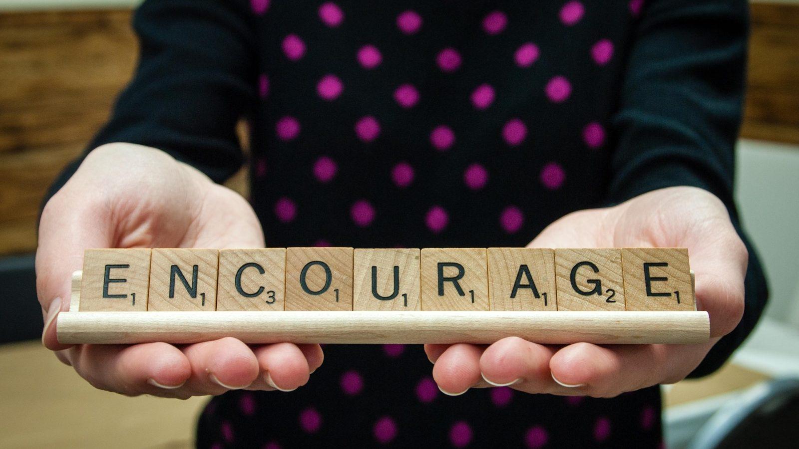 Photo d'illustation, une femme tient dans ses mains des pièce de scrabnle ecrivants le mot encourage